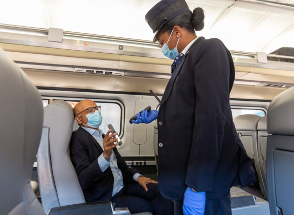 an amtrak worker useing contactless ticket scanning