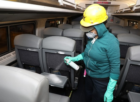 an amtrak worker disinfecting seats