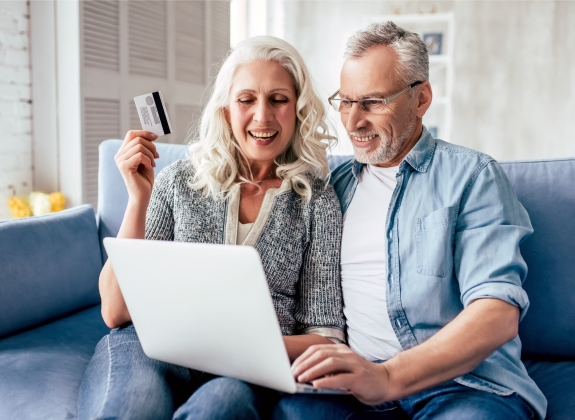 couple looking at a computer ready to book with a credit card