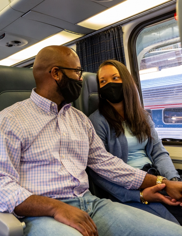 a happy couple onboard Amtrak in coach accommodations while wearing facial coverings