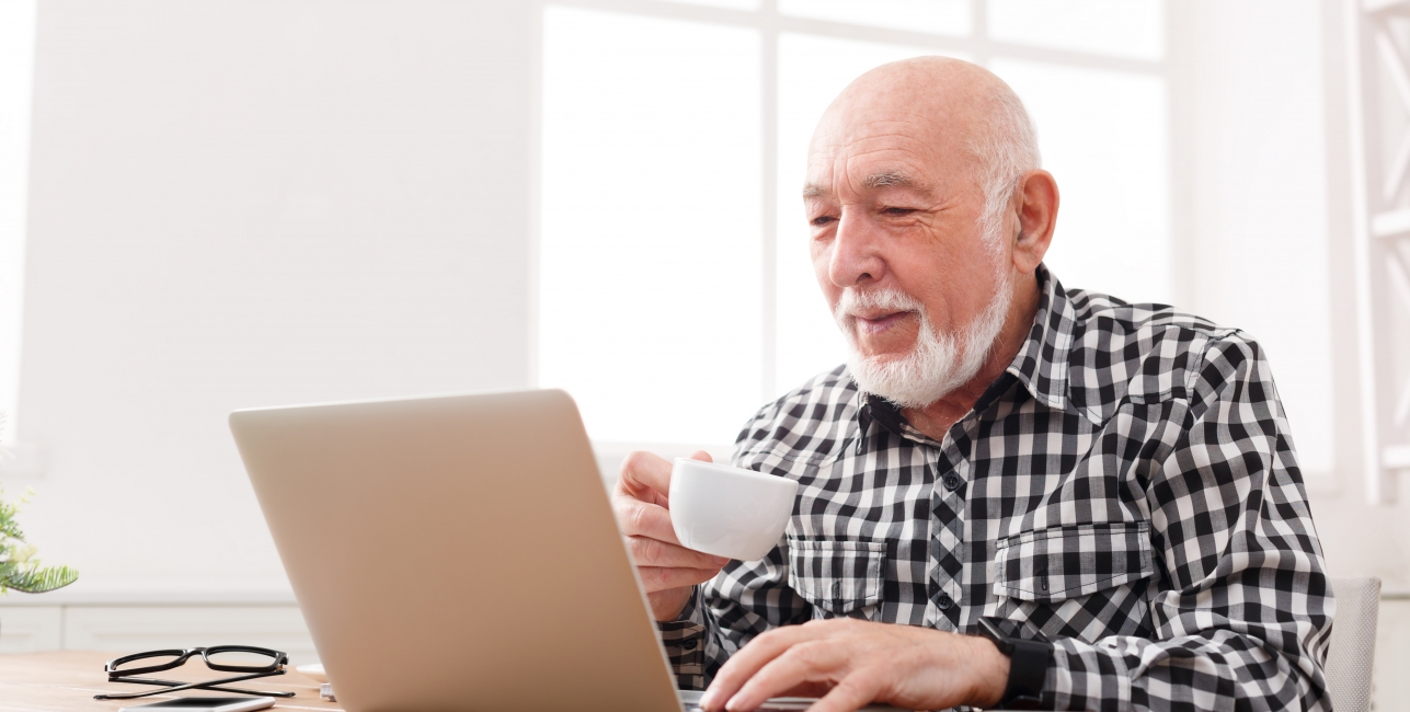 man watching computer screen and drinking a cup of tea