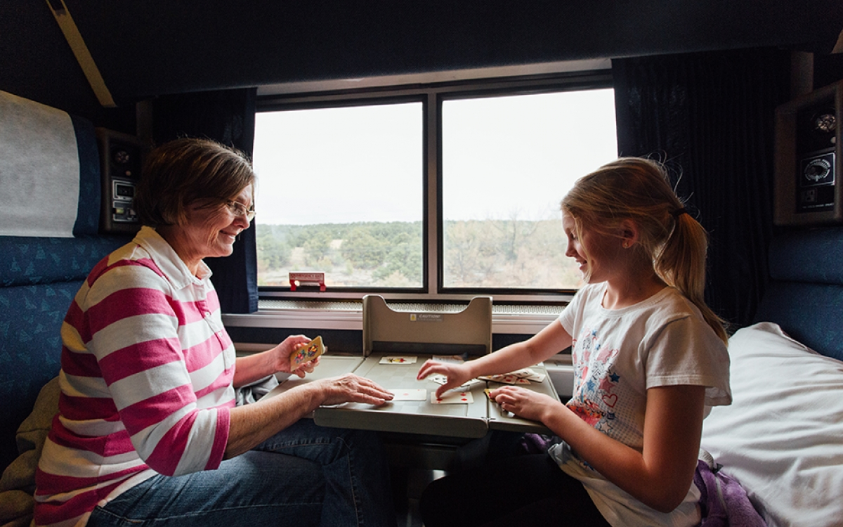 mother and daughter playing cards in their private room aboard Amtrak