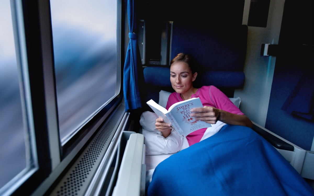 woman reading book in a roomette onboard amtrak