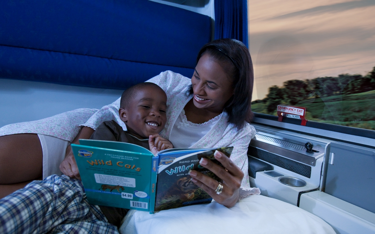 mom and child reading book in private room onboard amtrak