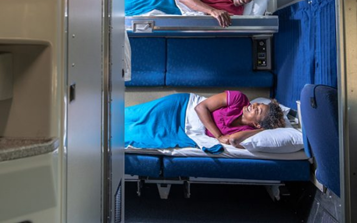 couple looking at each other from bunkbeds onboard amtrak