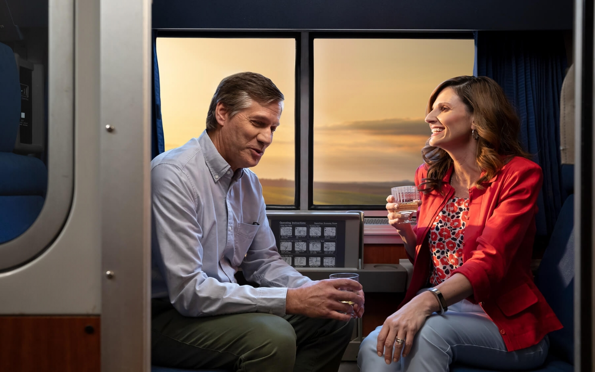 Man and woman drinking and laughing in roomette