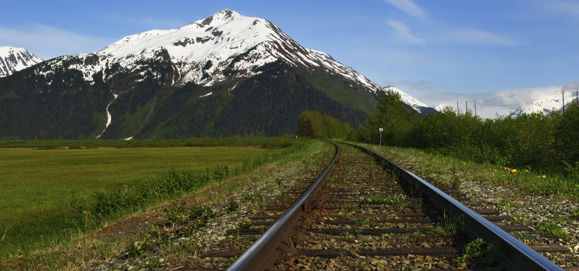 railroad tracks in Alaska by mountain view