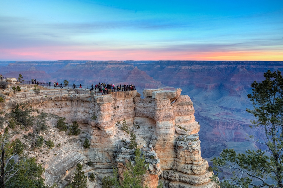 sunset image of the grand canyon where passengers are standing on the edge