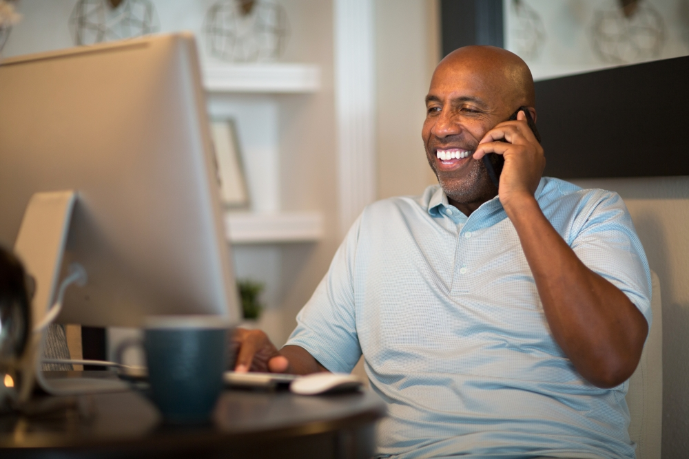a man talking on the phone in front of computer