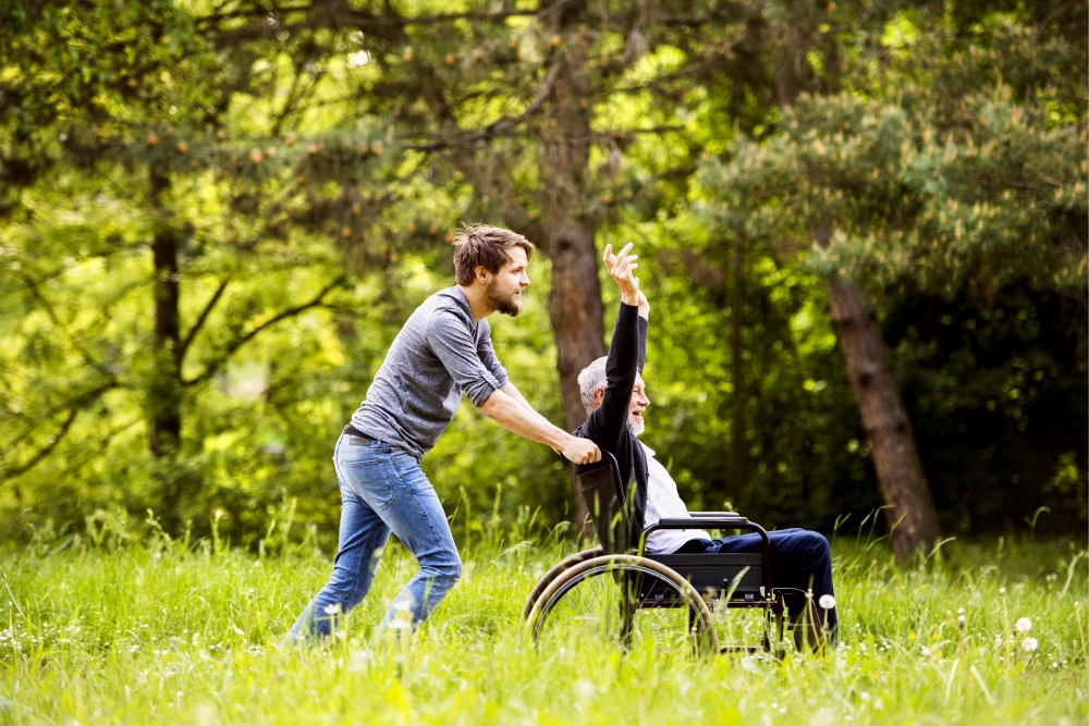 man pushing his father in a wheel chair through a field